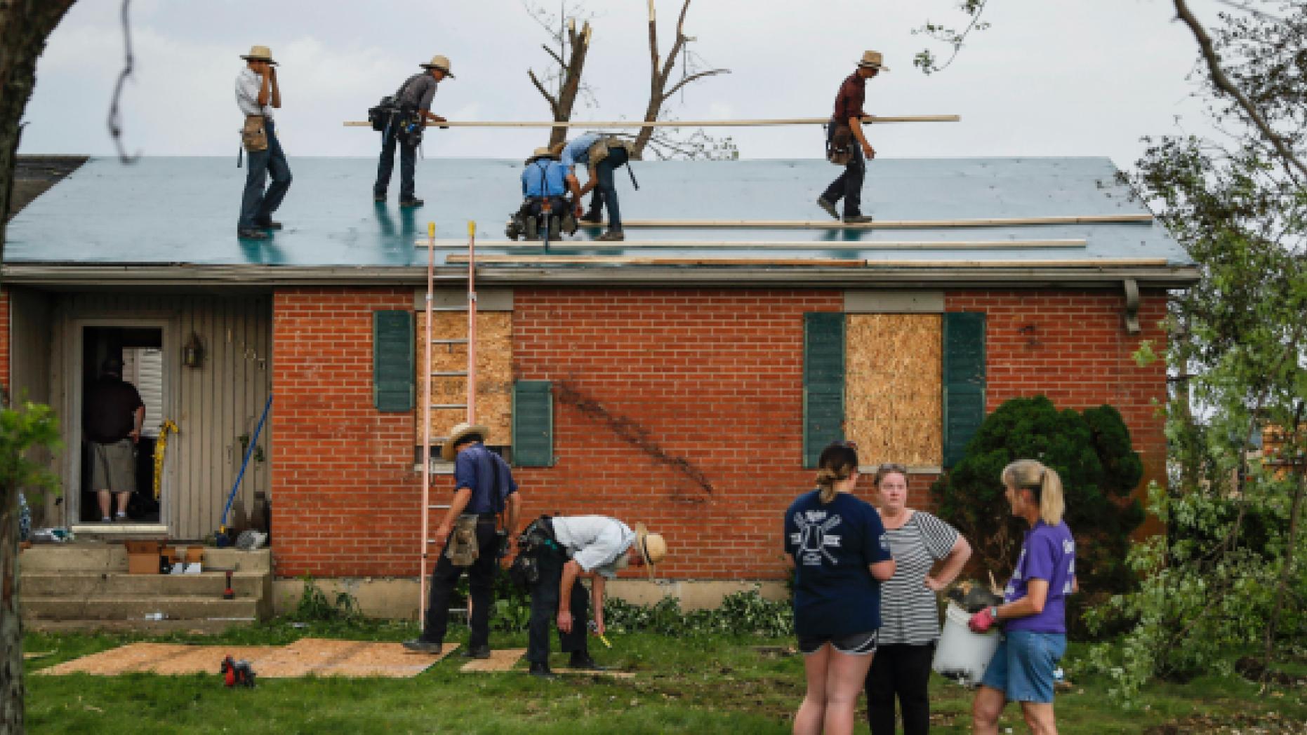 Residents and volunteers clean debris from damaged homes litters the properties on Fairground Road in Celina, Ohio, Tuesday, May 28, 2019, after a tornado storm system passed through the area the previous night. (AP Photo/John Minchillo)
