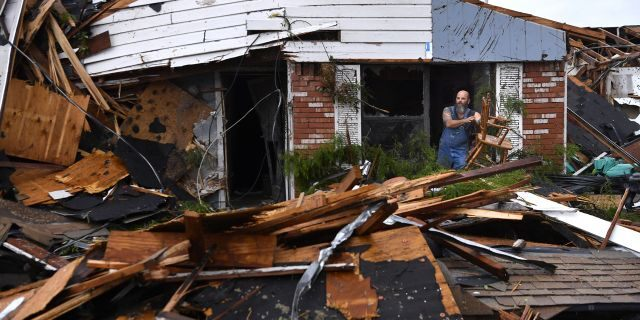 Wesley Mantooth lifts a wooden chair out a window of the home of his father, Robert, in Abilene, Texas, on Saturday, May 18, 2019.