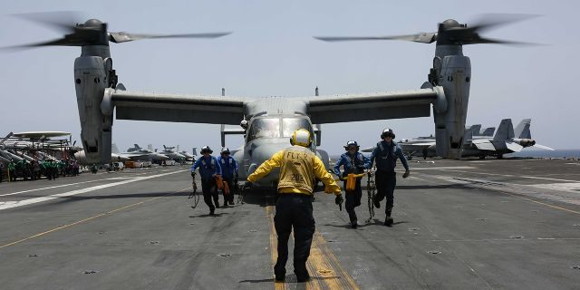 In this Friday, May 17, 2019, photo, released by the U.S. Navy, sailors work around an MV-22 Osprey as it lands on the flight deck of the Nimitz-class aircraft carrier USS Abraham Lincoln in the Arabian Sea.