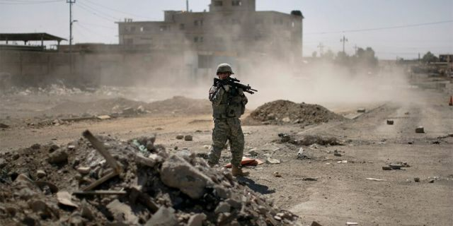 FILE -- June 19, 2008: A U.S. soldier secures the road while Major-General Mark Hertling, the commander of the U.S. forces in northern Iraq, holds a joint battlefield circulation patrol with U.S. and Iraqi soldiers on the streets in Mosul. REUTERS/Eduardo Munoz
