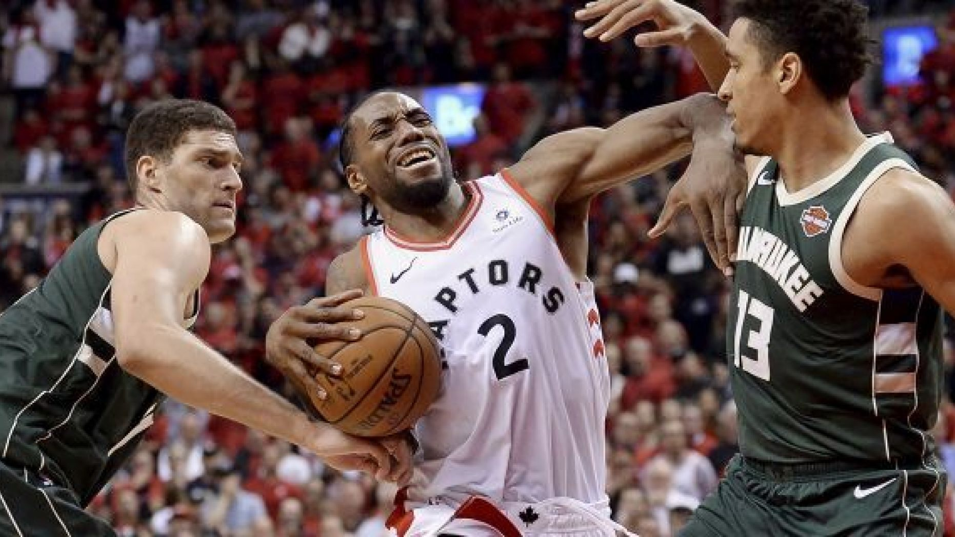 Toronto Raptors forward Kawhi Leonard (2) drives to the net against Milwaukee Bucks center Brook Lopez (11) and guard Malcolm Brogdon (13) during the second overtime period of Game 3 of the NBA basketball playoffs Eastern Conference finals in Toronto on Sunday, May 19, 2019. (Nathan Denette/The Canadian Press via AP)