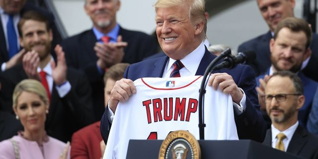 President Donald Trump shows off a Red Sox jersey presented to him during a ceremony welcoming the Boston Red Sox the 2018 World Series baseball champions to the White House. (AP Photo/Manuel Balce Ceneta)