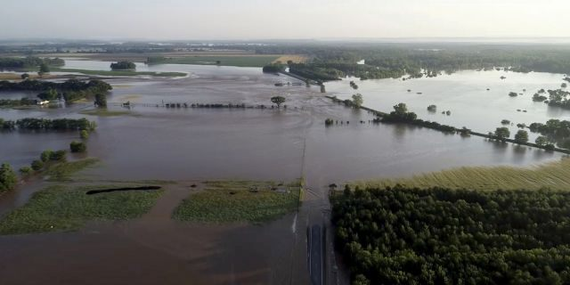 In this aerial image provided by Yell County Sheriff's Department water rushes through the levee along Arkansas River in Dardanelle, Ark., on Friday. Officials say the levee breached early Friday at Dardanelle, about 60 miles northwest of Little Rock. (Yell County Sheriff's Department via AP)