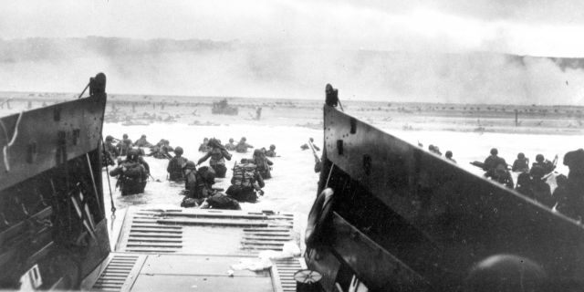 FILE - In this June 8, 1944, file photo, under heavy German machine gun fire, American infantrymen wade ashore off the ramp of a Coast Guard landing craft during the invasion of the French coast of Normandy in World War II. June 6, 2019, marks the 75th anniversary of D-Day, the assault that began the liberation of France and Europe from German occupation, leading to the end World War II. (U.S. Coast Guard via AP, File)
