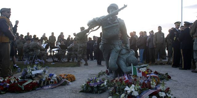 floral tributes are placed at the National Guard Monument Memorial as members of the USAREUR band play in the background near Omaha Beach, in Normandy, France, on Thursday. (Associated Press)