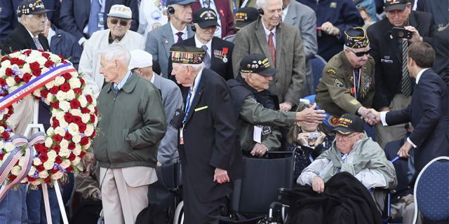 French President Emmanuel Macron, right, greets veterans during a ceremony to mark the 75th anniversary of D-Day at the Normandy American Cemetery in Colleville-sur-Mer, Normandy, France, on Thursday.
