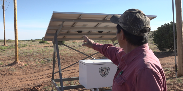 Ernest Littlefoot, Sr. shows the newly installed powerline poles near his home as part of the Light Up Navajo Project.