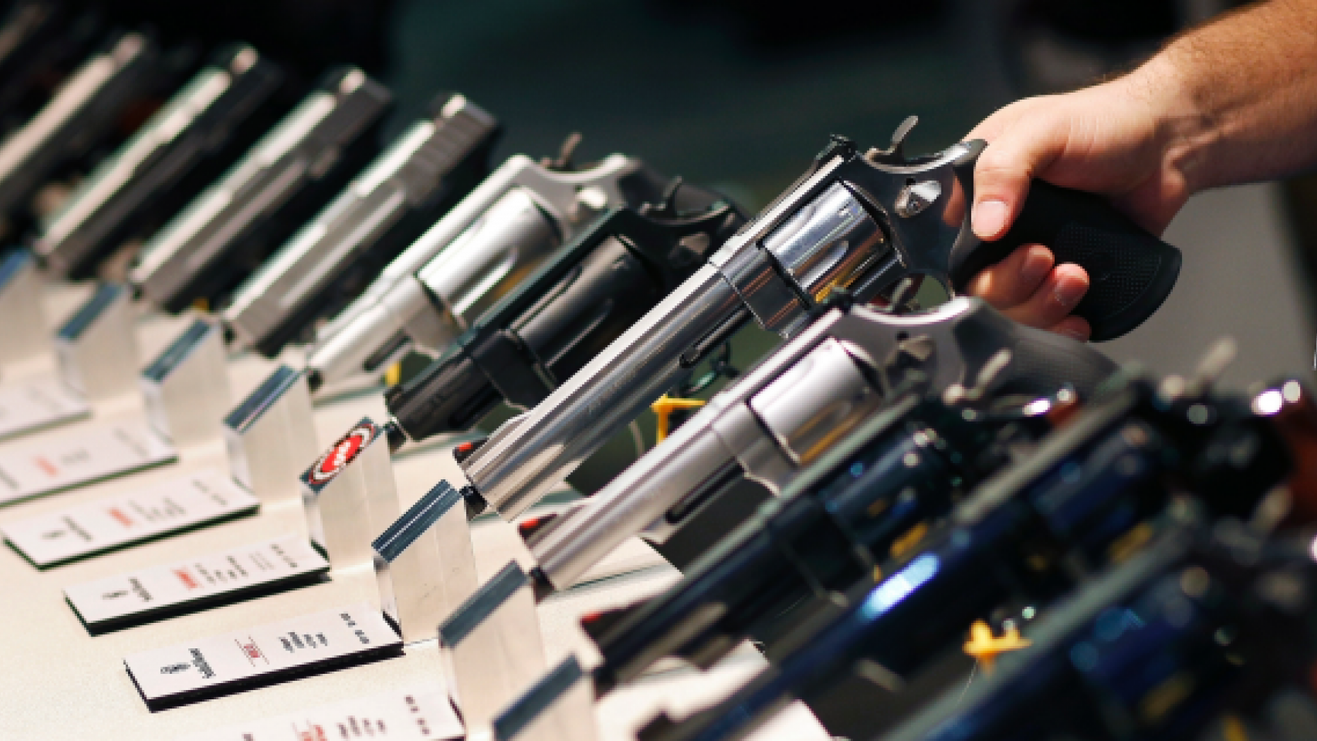 FILE - In this Jan. 19, 2016 file photo, handguns are displayed at the Smith & Wesson booth at the Shooting, Hunting and Outdoor Trade Show in Las Vegas. Two former trade show workers have pleaded guilty to federal firearms charges following the theft of weapons from the U.S. gun industry