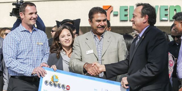 Hugo Lopez, right, resigned Friday as director of the California State Lottery. He is shown congratulating prize winners on Jan. 14, 2016, in Chino Hills, Calif. (Getty Images)
