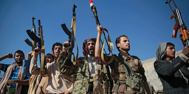 In this Dec. 13, 2018, file, photo, tribesmen loyal to Houthi rebels hold up their weapons as they attend a gathering to show their support for the ongoing peace talks being held in Sweden, in Sanaa, Yemen. The United Nations has cast doubt on the claims by Yemen's Shiite rebels to have withdrawn from the port of Hodeida, saying such steps can only be credible if all other parties can verify them.