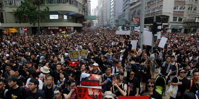 Tens of thousands of protesters march through the streets as they continue to protest an extradition bill, Sunday, June 16, 2019, in Hong Kong.