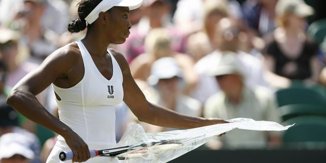 US Venus Williams removes a racketfrom a plastic bag during play against Spain