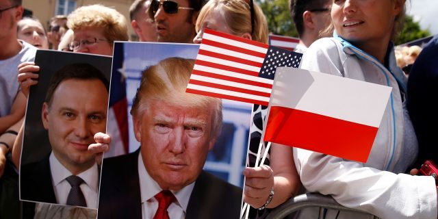 People holding portraits of President Trump and Polish President Andrzej Duda in July 2017.