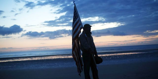 Udo Hartung from Frankfurt, Germany, a World War II reenactor, holds the U.S. flag as he stands at dawn on Omaha Beach, in Normandy, France on Thursday. (Associated Press)