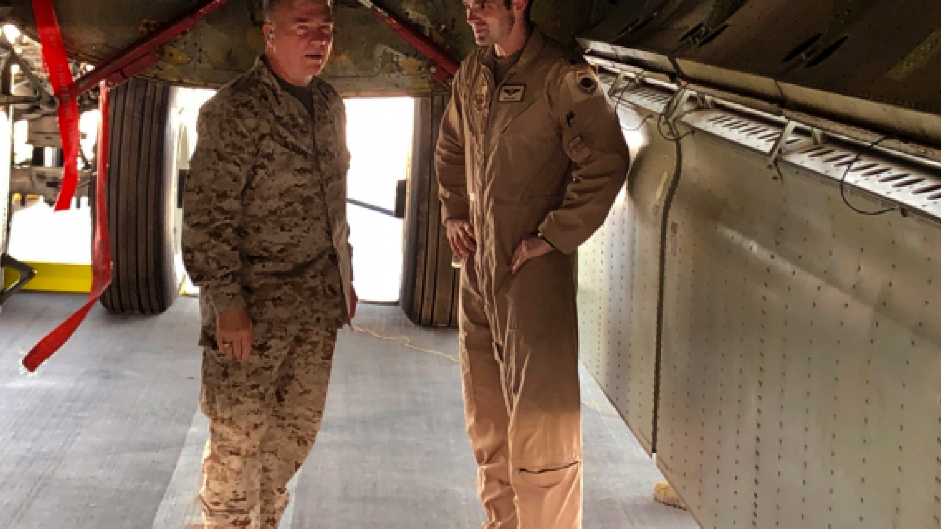 """Marine Gen. Frank McKenzie, head of U.S. Central Command, confers with an Air Force officer below the bomb bay of a B-52 bomber on Friday, June 7, 2019 at al-Udeid air base in Qatar. McKenzie said on Friday that he thinks Iran had been planning some sort of attack on shipping or U.S. forces in Iraq. Two other officials, speaking on condition of anonymity to discuss sensitive details, said Iran was at a high state of readiness in early May with its ships, submarines, surface-to-air missiles and drone aircraft.   """"It is my assessment that if we had not reenforced, it is entirely likely that an attack would have taken place by now,"""" he said.  (AP Photo/Robert Burns)"""