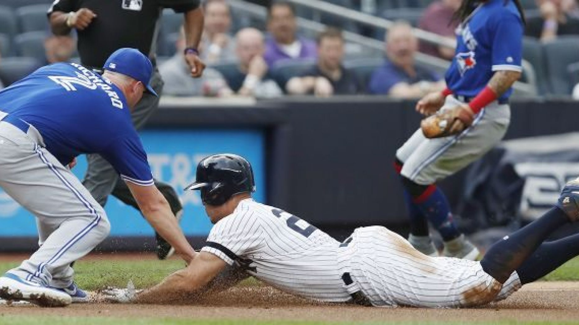 Toronto Blue Jays starting pitcher Clayton Richard, left, tags out New York Yankees