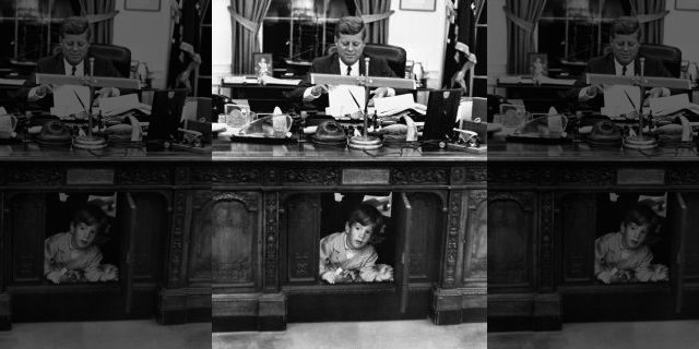 A young John F. Kennedy Jr. exploring his father's desk.