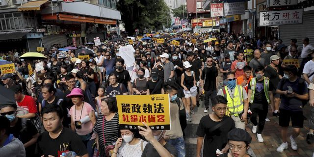 "Protesters hold up words that read: ""Strict enforcing of law against smugglers of grey goods"" in Hong Kong Saturday, July 13, 2019. Several thousand people are marching in Hong Kong against traders from mainland China in what is fast becoming a summer of unrest in the semi-autonomous Chinese territory. (AP Photo/Kin Cheung)"