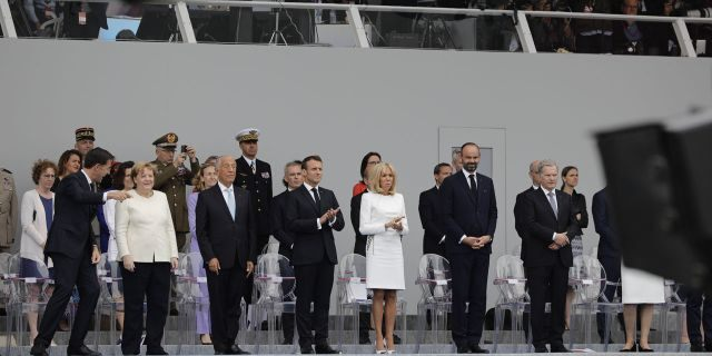 From the left, Dutch Prime Minister Mark Rutte, German Chancellor Angela Merkel, Portugal's President Marcelo Rebelo de Sousa, French President Emmanuel Macron, his wife Brigitte, French Prime Minister Edouard Philippe and Finnish President Sauli Niinisto attend Bastille Day parade Sunday, July 14, 2019, on the Champs Elysees avenue in Paris