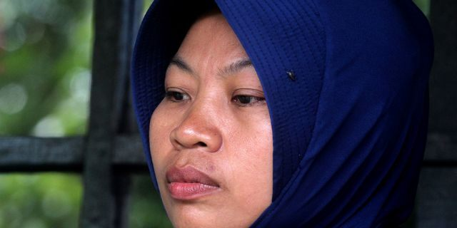 Baiq Nuril Maknun, who exposed her cheating boss, looks stunned after she got slapped with a six-month jail term for violating a controversial law against spreading indecent material, in Mataram on Lombok island on November 16, 2018. - The supreme court