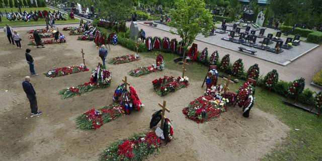 People lay flowers at the graves of the 14 crew members who died in a fire on a Russian navy