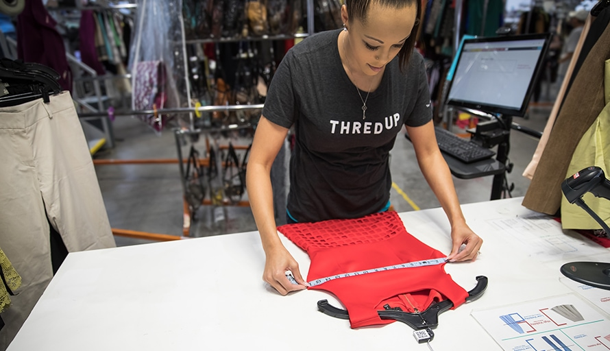 woman measuring clothes for resale on thredup