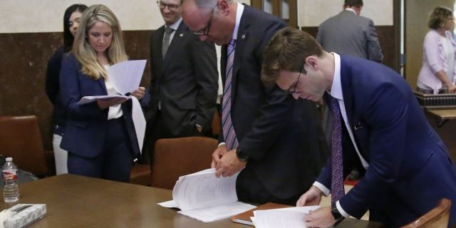 Attorneys for the state looking over court documents following Judge Thad Balkman's announcement of his decision. (AP Photo/Sue Ogrocki, Pool)