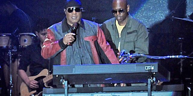 """Musician Stevie Wonder, front left, and comedian Dave Chappelle appear on stage during the """"Gem City Shine,"""" event in the Oregon District in Dayton, Ohio, Sunday, Aug. 25, 2019. Chappelle, who resides in nearby Yellow Springs, hosted the special block party and benefit concert for those affected by the recent mass shooting."""