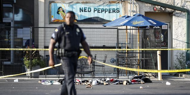 Shoes are piled outside the scene of a mass shooting including Ned Peppers bar, Sunday, Aug. 4, 2019, in Dayton, Ohio. (Associated Press)