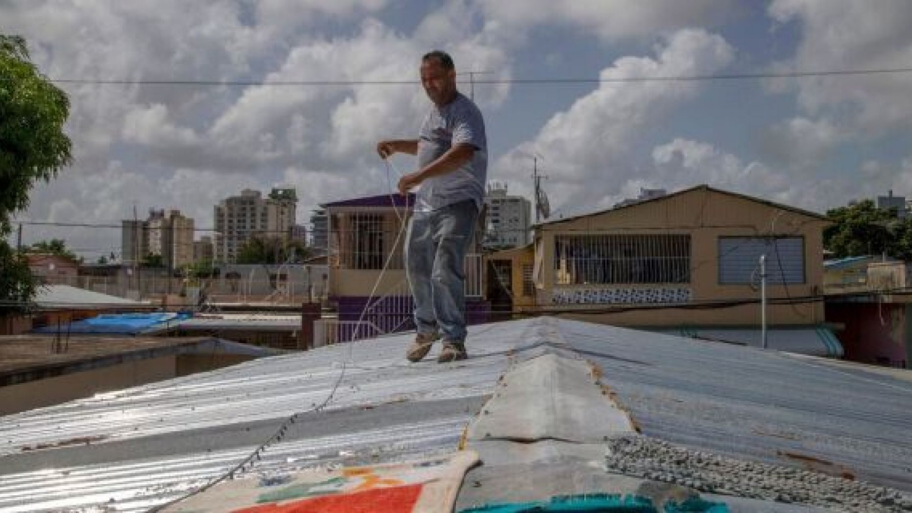 Jorge Ortiz works to tie down his roof as he prepares for the arrival of Tropical Storm Dorian, in the Martín Peña neighborhood of San Juan, Puerto Rico. (AP Photo/Gianfranco Gaglione)