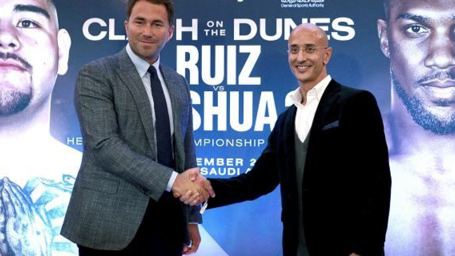 Boxing promoters Eddie Hearn and managing partner of Skill Challenge Entertainment Omar Khalil shake hands, during a press conference at The Savoy Hotel, London, Monday, Aug. 12, 2019. Anthony Joshua