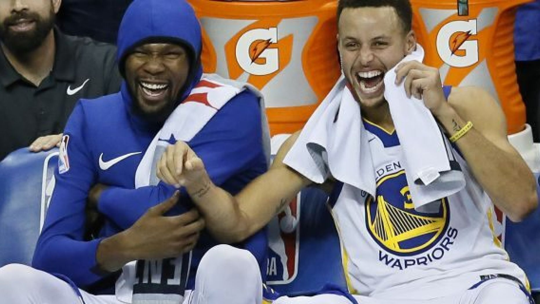 FILE - In this Nov. 22, 2017, file photo, Golden State Warriors forward Kevin Durant, left, and guard Stephen Curry, right, laugh on the bench during the third quarter of the team