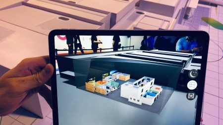 Hand holding an iPad tablet that displays an architectural augmented reality graphic