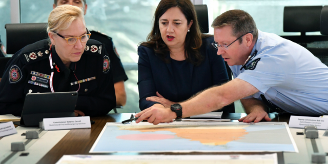 In this March 19, 2019, photo, Queensland Fire and Emergency Services Commissioner, Katarina Carroll (left), Queensland Premier Annastacia Palaszczuk (center) and Queensland Police Deputy Commissioner Bob Gee (right) are seen during a meeting of the Queensland Disaster Management Committee discussing the approaching cyclone at the Emergency Services Complex in Brisbane. Australia is evacuating about 2,000 people from part of northern Australia ahead of powerful Cyclone Trevor expected to hit on Saturday.