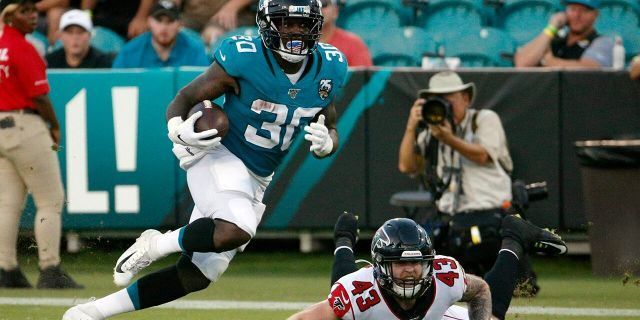 Jacksonville Jaguars running back Ryquell Armstead (30) runs past Atlanta Falcons defensive back Parker Baldwin (43) during the first half of an NFL preseason football game Thursday, Aug. 29, 2019, in Jacksonville, Fla. (AP Photo/Stephen B. Morton)