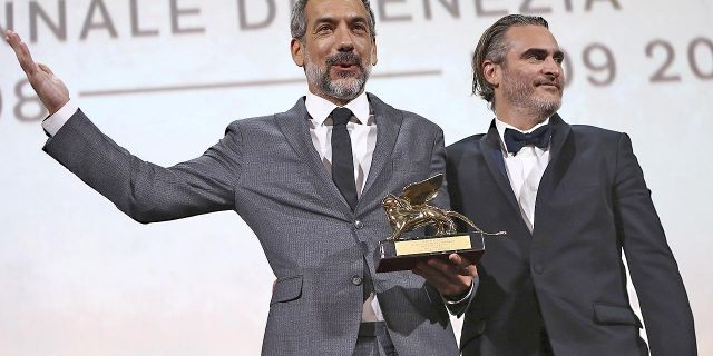 """Director Todd Phillips, left, holds the Golden Lion for Best Film for """"Joker,"""" joined by lead actor Joaquin Phoenix at the closing ceremony of the 76th edition of the Venice Film Festival, Venice, Italy, Saturday, Sept. 7, 2019."""