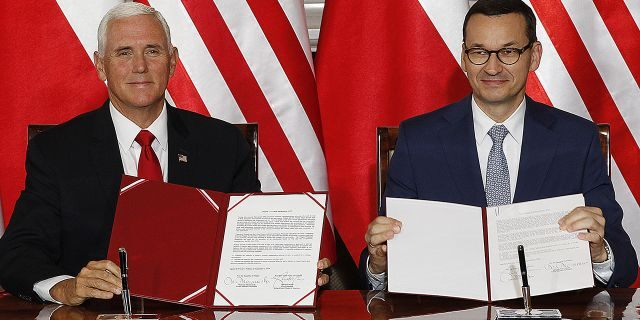 U.S. Vice President Mike Pence and Polish Prime Minister Mateusz Morawiecki, right, exchange copies of an agreement they signed in Warsaw, Poland, Monday, Sept. 2, 2019. (AP Photo/Czarek Sokolowski)